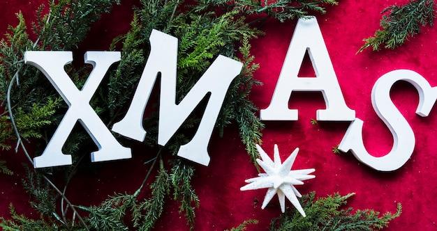 Titolo di natale tra rami di conifere verdi e stella di ornamento