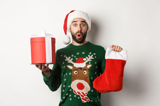 Natale e concetto di vacanze invernali. uomo emozionante che tiene calza di natale e confezione regalo, festeggiando il nuovo anno, in piedi su sfondo bianco.