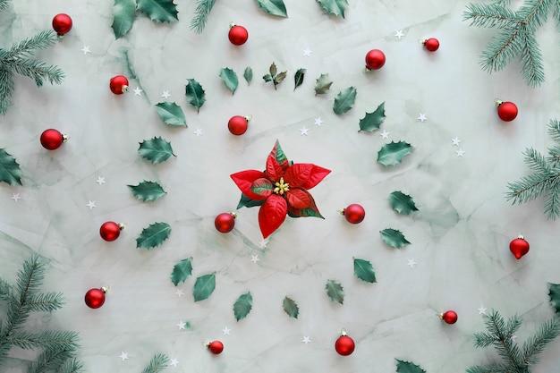 緑の自然なモミの小枝、ヒイラギの葉、赤いガラスのつまらないクリスマス。