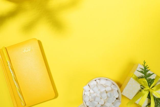 Xmas концепция рабочего пространства в желтом цвете. блокнот-органайзер на 2021 год, чашка кофе с зефиром, подарочная коробка своими руками, тени еловых веток на желтом. подведение итогов, планирование. вид сверху, плоская планировка, копия пространства.