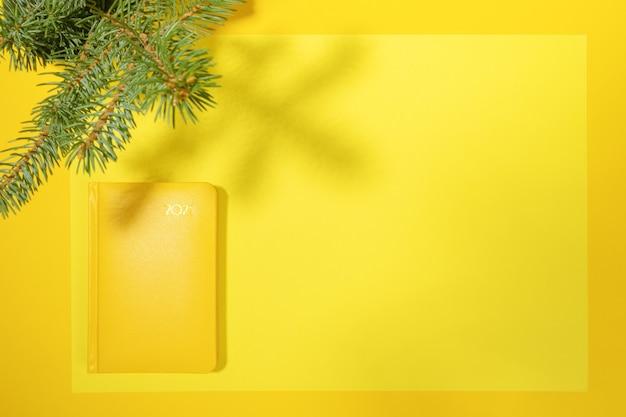 Xmas концепция рабочего пространства. желтый блокнот-органайзер 2021 года на пустом листе с копией пространства и еловыми ветками и тенями сверху на желтом. подведение итогов, планирование. вид сверху.