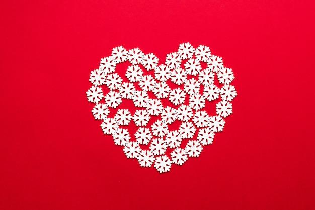 Новогодняя современная композиция. xmas снег сердце украшения на красном фоне