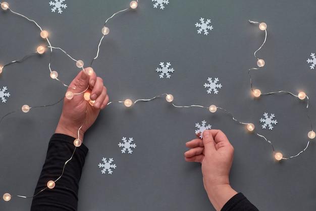 Зимний праздничный праздничный состав. рука керамическая ель украшения. новогоднюю или рождественскую квартиру заложить. руки держат легкую гирлянду и снежинку. надземный взгляд xmas на серой бумажной предпосылке.