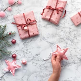 Рождественская квартира лежала на мраморном столе, квадратная композиция. женская рука декоративные звезды xmas. зимние украшения: еловые веточки и розовые безделушки.