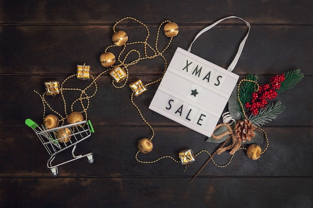 Слово xmass sale на лайтбоксе и небольшой корзине с золотыми подарками на деревянном фоне.