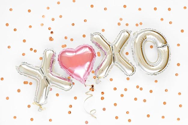 Буквы на воздушном шаре из фольги xoxo и воздушный шар в форме сердца. концепция любви. праздник и торжество. день святого валентина или украшение свадьбы / девичника. красочные металлические воздушные шары.