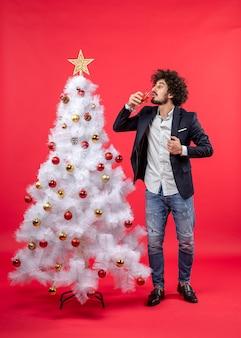 Celebrazione di natale con il giovane barbuto che beve il suo vino in piedi vicino all'albero di natale sul rosso
