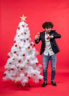 Xsmas celebration with bearded young man with wine checking time and standing near christmas tree on red
