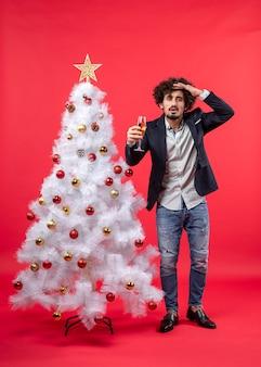 Celebrazione di natale con il giovane barbuto con vino concentrato su qualcosa con attenzione