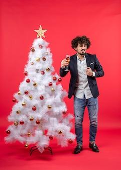 Celebrazione di natale con il giovane barbuto con vino che dice qualcosa in piedi vicino all'albero di natale sul rosso
