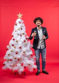 赤のクリスマスツリーの近くに立っているワインとひげを生やした若い男とクリスマスのお祝い