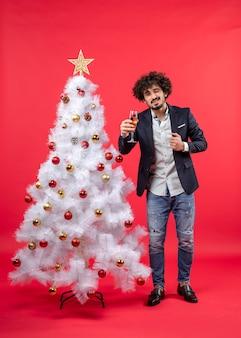 Рождественский праздник с бородатым молодым человеком с вином, смотрящим в камеру и стоящим возле елки на красном