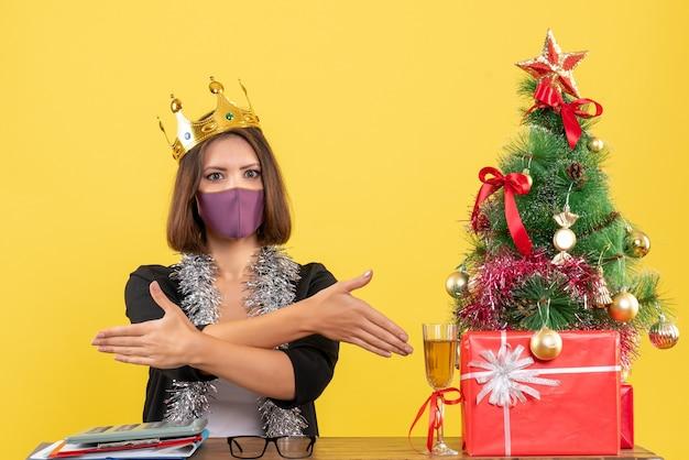 의료 마스크와 양복에 아름다운 아가씨와 노란색에 사무실에서 그녀의 손님을 환영하는 마스크를 쓰고 크리스마스 분위기