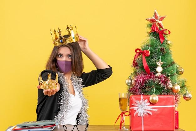 Atmosfera natalizia con bella signora in vestito con mascherina medica e che tiene le corone sulla testa e nella mano in ufficio su giallo