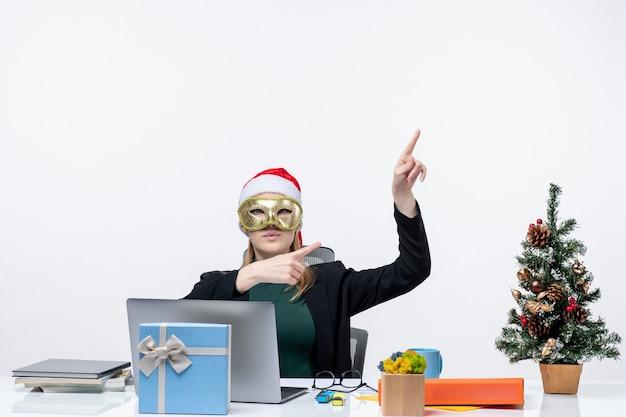 Atmosfera natalizia con giovane donna bionda con cappello di babbo natale e maschera da indossare seduti a un tavolo rivolto in alto sul lato sinistro su sfondo bianco