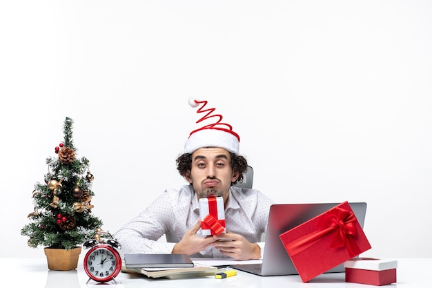 Xsmas mood with busy young businessman with santa claus hat sitting in the office and holding his gift posing for camera on white background