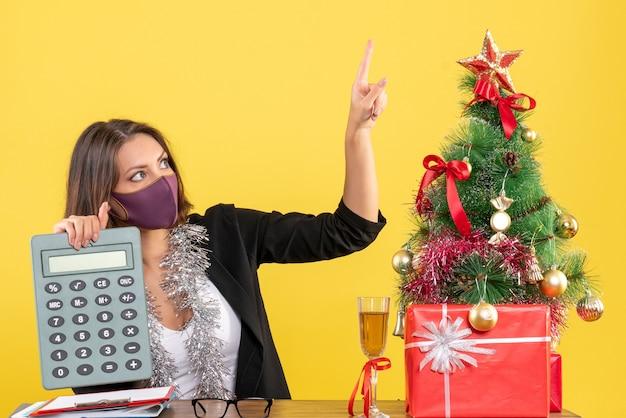 黄色のオフィスで上向きの計算機を保持している医療マスクを身に着けているスーツの集中した美しい女性とxsmas気分