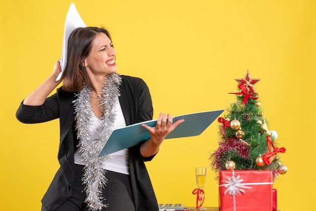 집중된 아름다운 여인이 사무실에 서서 노란색 문서를 조사하는 크리스마스 분위기