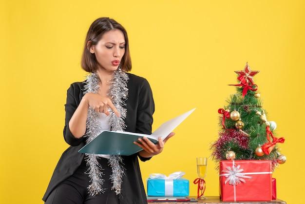 Atmosfera natalizia con bella signora concentrata in piedi in ufficio e lavorando da sola in ufficio su giallo