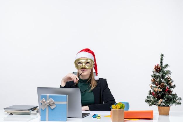 Atmosfera natalizia con fiduciosa giovane donna con cappello di babbo natale tenendo gli occhiali e indossando la maschera seduto a un tavolo su sfondo bianco