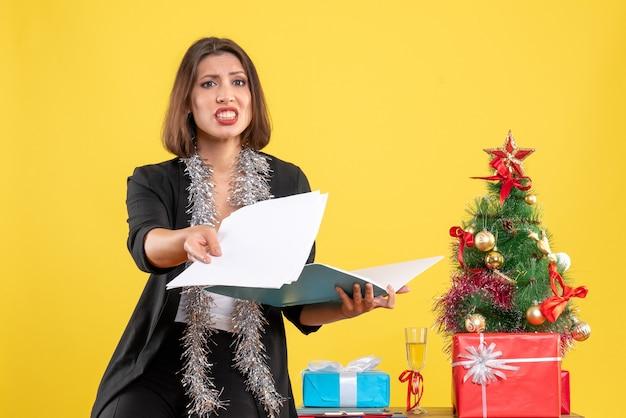 Atmosfera natalizia con bella signora confusa in piedi in ufficio e lavorando da sola in ufficio su giallo