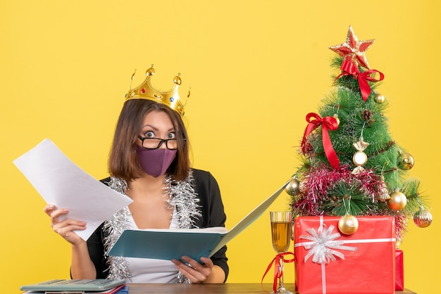 Umore di natale con bella signora confusa in vestito con la corona da portare con la sua mascherina medica che tiene i documenti nell'ufficio su colore giallo