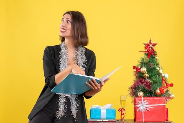 Atmosfera natalizia con curiosa bella signora in piedi in ufficio e lavorando da sola in ufficio su giallo