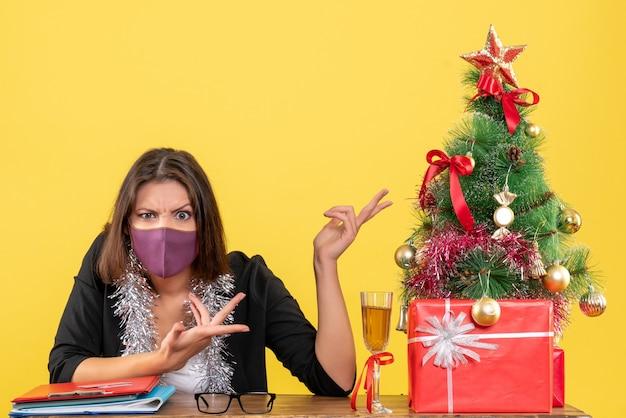 Рождественское настроение с любопытной очаровательной дамой в костюме в медицинской маске в офисе на желтом изолированном