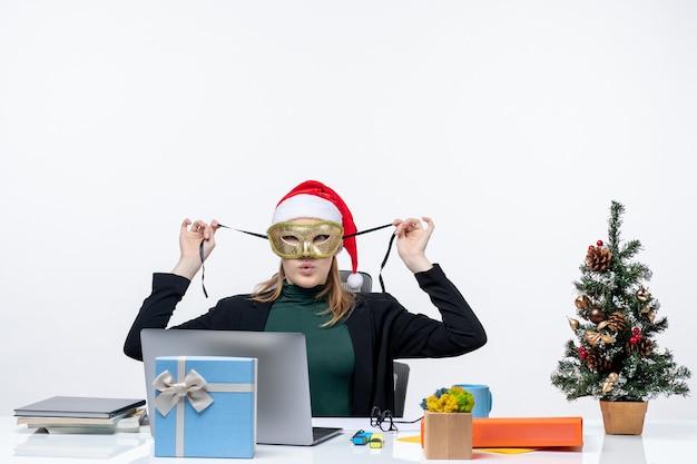 Atmosfera natalizia con curiosa giovane donna con cappello di babbo natale e maschera da portare seduto a un tavolo su sfondo bianco