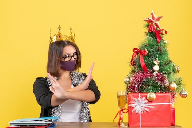 노란색에 사무실에서 중지 제스처를 만드는 그녀의 의료 마스크로 왕관을 쓰고 정장에 결정적인 아름다운 아가씨와 함께 크리스마스 분위기