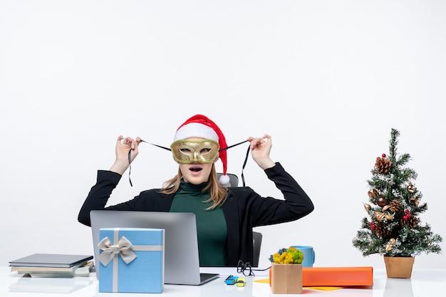 Umore natalizio con giovane donna emotiva con cappello di babbo natale e maschera da portare seduto a un tavolo su sfondo bianco