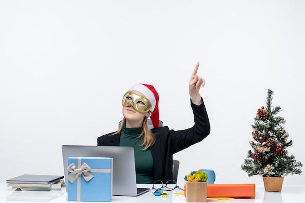 Umore natalizio con eccitata giovane donna positiva con cappello di babbo natale e maschera da portare seduto a un tavolo che punta sopra su uno sfondo bianco