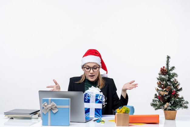 Xsmas mood with excited young woman with santa claus hat and wearing eyeglasses sitting at a table looking at gift surprisingly on white background