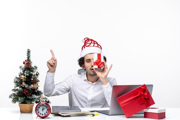 Рождественское настроение с забавным деловым человеком в шляпе санта-клауса, поднимающим подарок к его лицу и указывающим выше на белом фоне