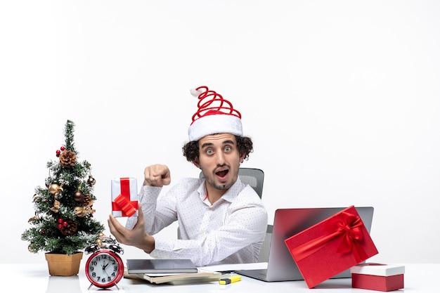 Umore di natale con il giovane uomo d'affari emotivo divertente con il cappello di babbo natale e indicando il suo regalo su priorità bassa bianca
