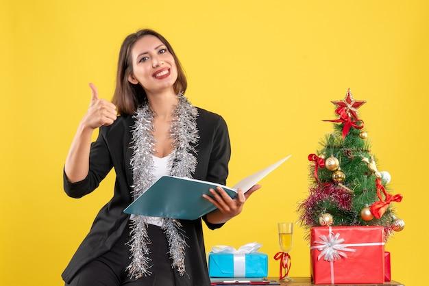 オフィスに立って一人で働いている笑顔の美しい女性がオフィスで大丈夫なジェスチャーをしているxsmasムード