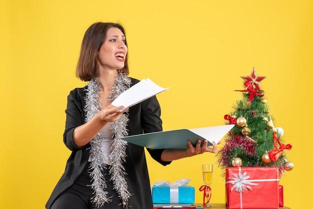 Atmosfera natalizia con sorridente bella signora in piedi in ufficio e indagando sui documenti che fanno domande