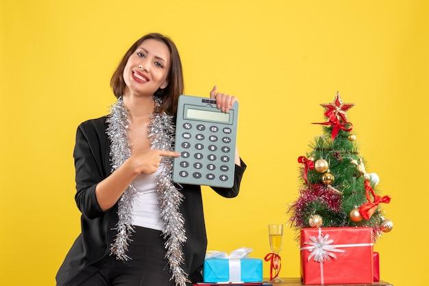 Atmosfera natalizia con sorridente bella signora in piedi in ufficio e mostrando la calcolatrice in ufficio