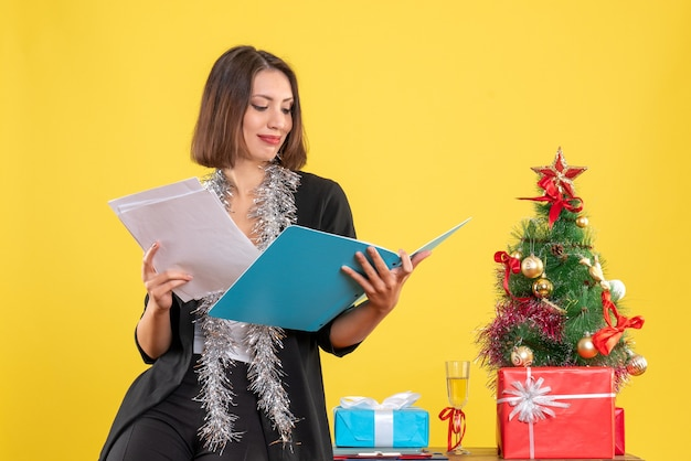 Xsmas mood with smiling beautiful lady standing in the office and working alone in the office