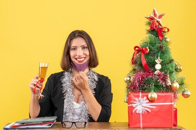 Atmosfera natalizia con sorridente bella signora in tuta che apre la mascherina medica e alza il vino in ufficio