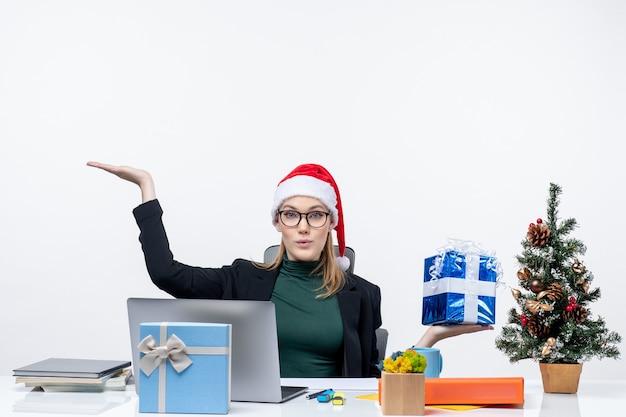 Atmosfera natalizia con giovane donna sorpresa con cappello di babbo natale e occhiali da vista seduti a un tavolo che mostra il dono che indica qualcosa su sfondo bianco