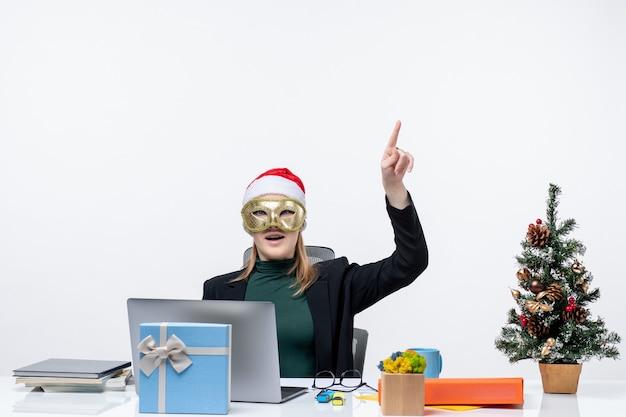 Atmosfera natalizia con giovane donna sorpresa con cappello di babbo natale e maschera da indossare seduto a un tavolo rivolto verso l'alto facendo domande su sfondo bianco