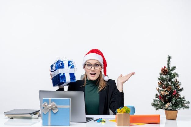 Umore di natale con sorprese giovane donna con cappello di babbo natale e occhiali da vista seduto a un tavolo tenendo il suo regalo su sfondo bianco