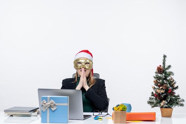 Рождественское настроение с напряженной молодой женщиной в шляпе санта-клауса и в маске, сидящей за столом на белом фоне