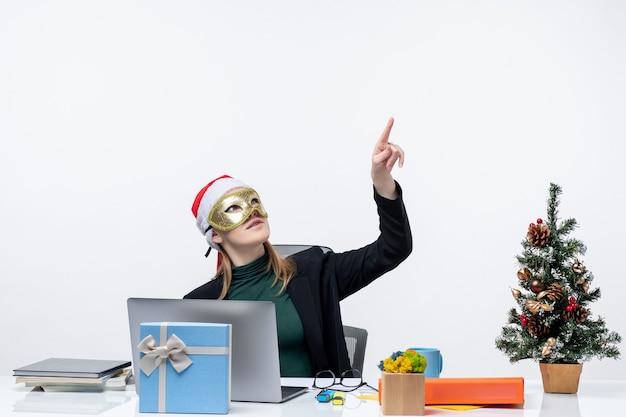 Рождественское настроение с напряженной молодой женщиной в шляпе санта-клауса и в маске, сидящей за столом, направленной вверх на белом фоне