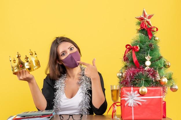 사무실에서 그녀의 의료 마스크를 쓰고 왕관을 들고 양복에 사려 깊은 아름다운 아가씨와 함께 크리스마스 분위기