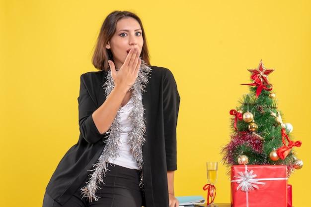 사려 깊은 아름다운 아가씨가 서서 사무실에서 신중하게 무언가를 찾고있는 크리스마스 분위기