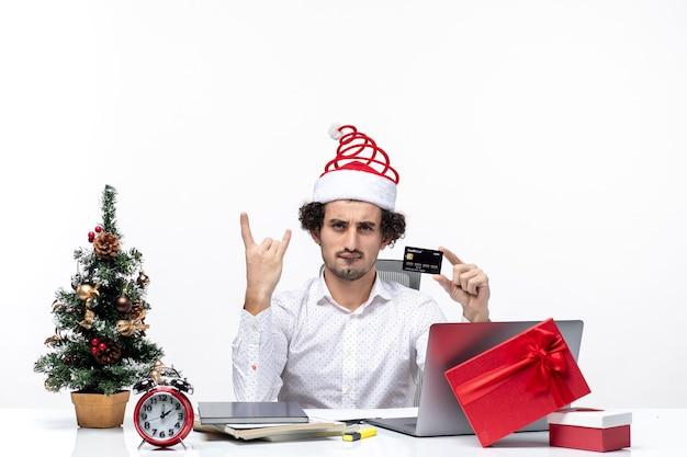 白い背景の上の銀行カードを保持しているサンタクロースの帽子を持つ若いひげを生やしたビジネスパーソンとxsmas気分