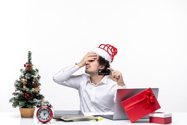 銀行カードを保持し、オフィスで上を指しているサンタクロースの帽子を持つ若いひげを生やした疲れたビジネスパーソンとxsmas気分