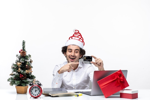 Umore di natale con giovane barbuto uomo d'affari positivo con cappello di babbo natale che tiene e puntando la carta di credito su sfondo bianco